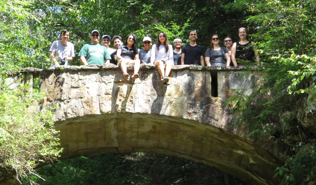 A photo of several spanish graduate students standing on a stone bridge in a heavily wooded area